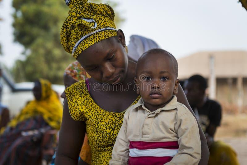 Ortrait μιας νέας μητέρας και του γιου της, στη γειτονιά Bissaque στην πόλη του Μπισσάου στοκ εικόνες