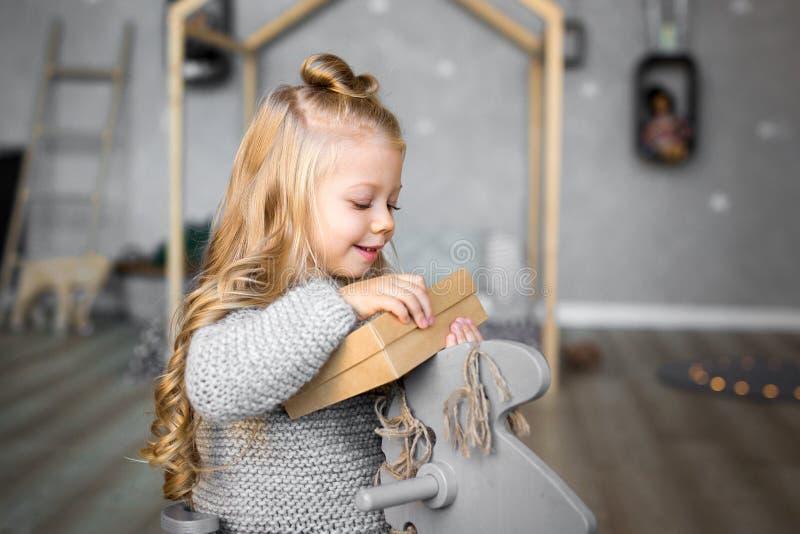 Ortrait de una muchacha sonriente feliz que abre una caja de regalo imagen de archivo