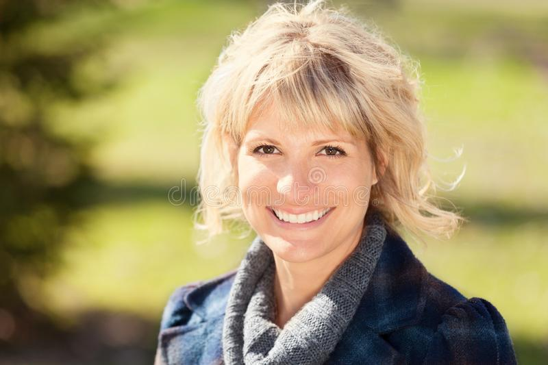 Ortrait Of A Mature Woman Smiling At The Camera. She is really Happy in summertime royalty free stock images