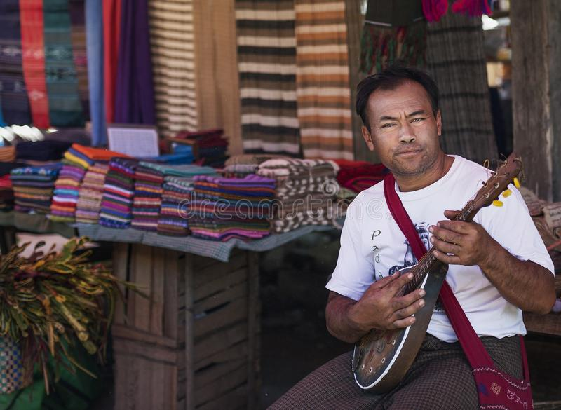 Ortrait of playing traditional music instrument outside his shop in local market, Inle Myanmar. Myanmar December 2014: Portrait of playing traditional music stock photos