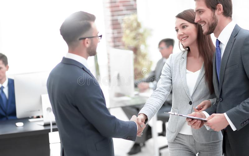Young man introducing himself at meeting to his partners. Ortrait of two smiling business people in suits making agreement, greeting each other, shaking hands royalty free stock photography