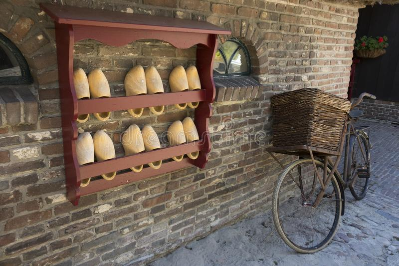 Orvelte, Drenthe, Netherlands - July 14, 2018: Traditional wooden shoes and an old bike in front of a farmhouse in Orvelte stock photography