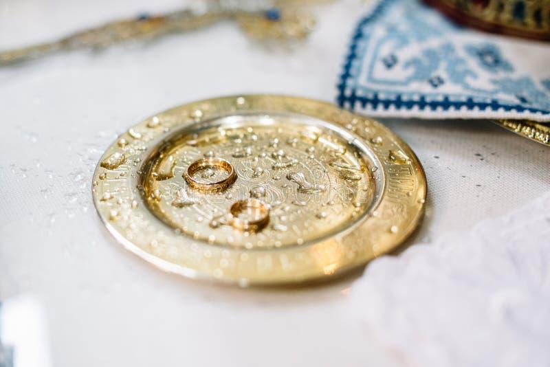 Oryginalne obrączki ślubne kłamają na stalowym talerzu na stole w chur obrazy royalty free