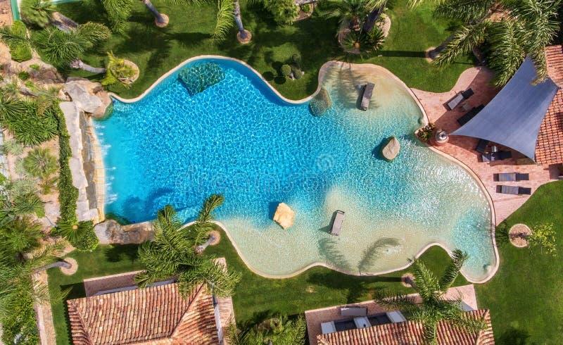 Oryginalny dekoracyjny basen w ogródzie z drzewkami palmowymi, widok z lotu ptaka obraz stock