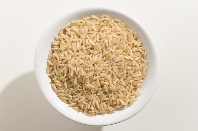 Whole Chinese Rice seed. Top view of grains in a bowl. White ba royalty free stock photography