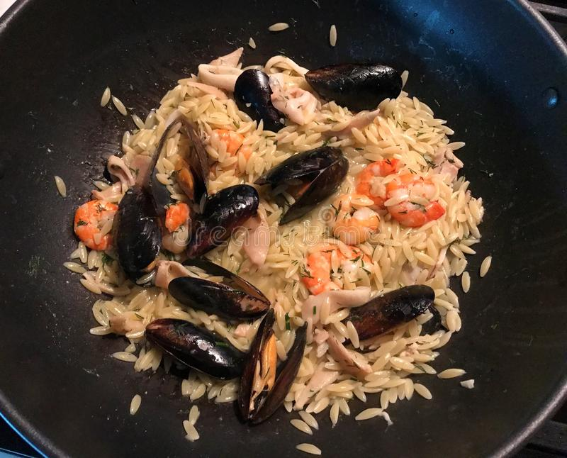 Orzo Palermo italiano with squid, shrimp and mussels. royalty free stock photos