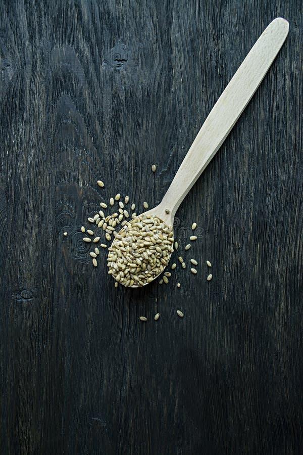 Orzo perlato in un cucchiaio di legno su un fondo di legno scuro Vista laterale fotografie stock libere da diritti