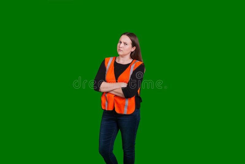 Osäker blick på armar för unga kvinnor som korsas på den gröna skärmbakgrunden royaltyfria bilder
