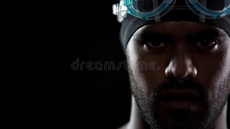 Os óculos de proteção vestindo do nadador latino-americano masculino, olhando diretamente na câmera, ostentam fotografia de stock