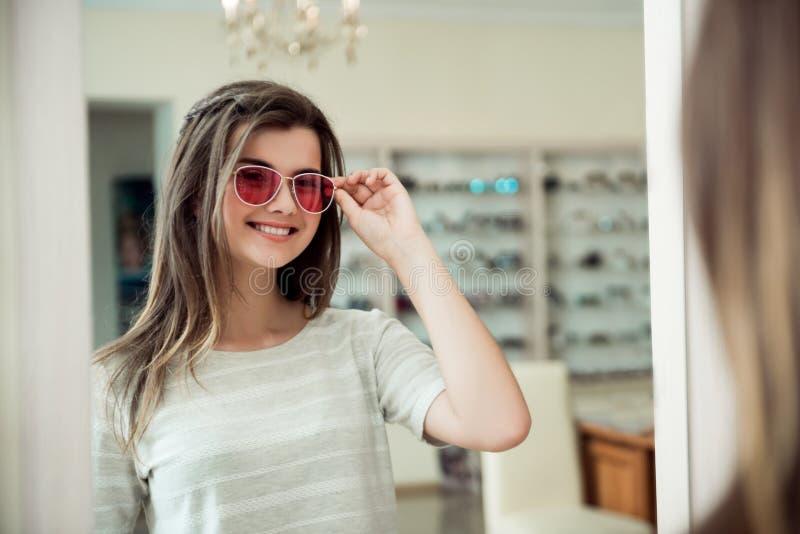 Os óculos de sol à moda fazem o olhar da pessoa elegante Retrato da menina europeia nova bonita de sorriso na loja do ótico fotos de stock