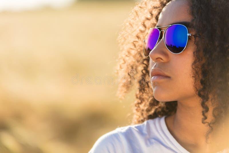 Os óculos de sol adolescentes da menina afro-americano da raça misturada aperfeiçoam os dentes imagem de stock