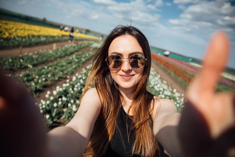 Os óculos de sol bonitos novos do desgaste de mulher fazem o selfie no campo de flor das tulipas no dia de mola ensolarado foto de stock royalty free