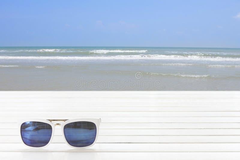 Os óculos de sol colocam na tabela de madeira com mar e praia fotografia de stock