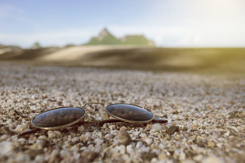 Os óculos de sol do vintage puseram sobre muitos corais pequenos quebrados, sucata do shell do mar sobre a areia com o céu azul b foto de stock royalty free