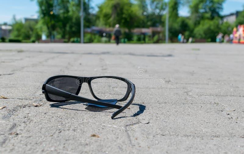 Os óculos de sol quebrados encontram-se em uma passagem pedra-telhada no parque da cidade imagens de stock royalty free