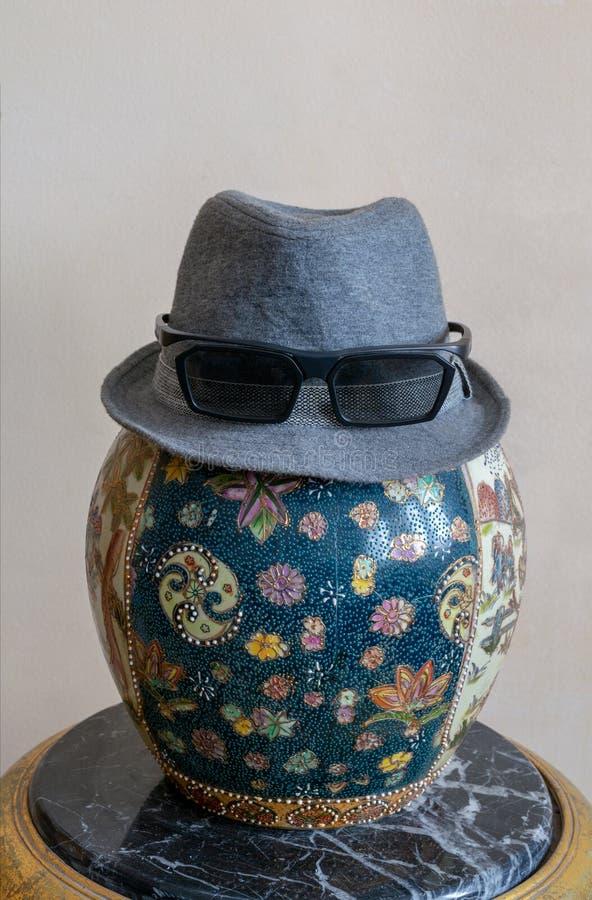 Os óculos de sol vestindo do chapéu do chapéu mole sobre a antiguidade decoraram o vaso cerâmico chinês do frasco sobre a tabela  foto de stock royalty free