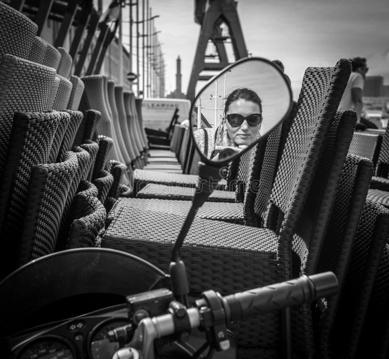 Os óculos de sol vestiram o motorista fêmea refletido no 'trotinette' da rua foto de stock royalty free