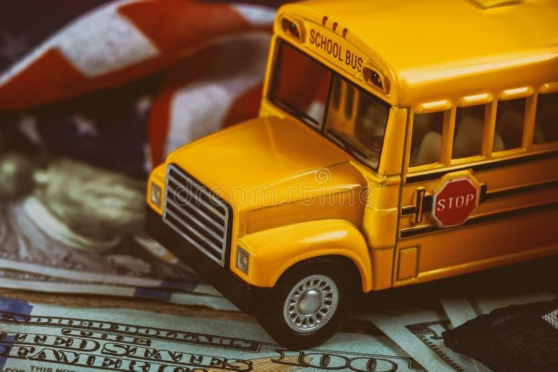 Os ônibus escolares, dólares americanos descontam o dinheiro e a bandeira dos EUA Fim acima imagem de stock royalty free