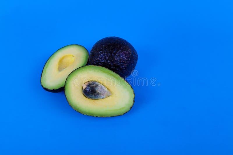 Os abacates inteiros e cortados pit mostrar no fundo azul fotografia de stock