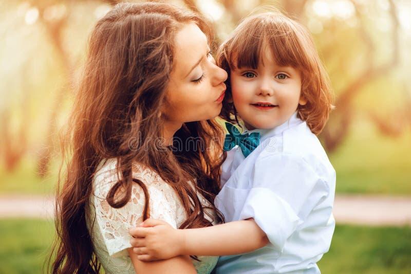 os abraços da mamã e a criança felizes do beijo caçoam o filho exterior na mola ou no verão Dia loving da família e de mães imagens de stock