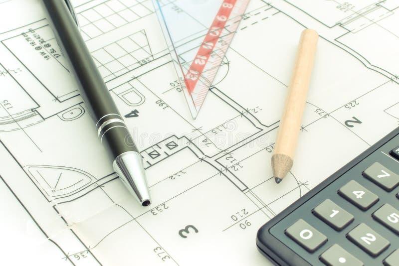 Os acessórios e a calculadora do desenho no alojamento planeiam, o conceito home do custo da construção fotos de stock royalty free