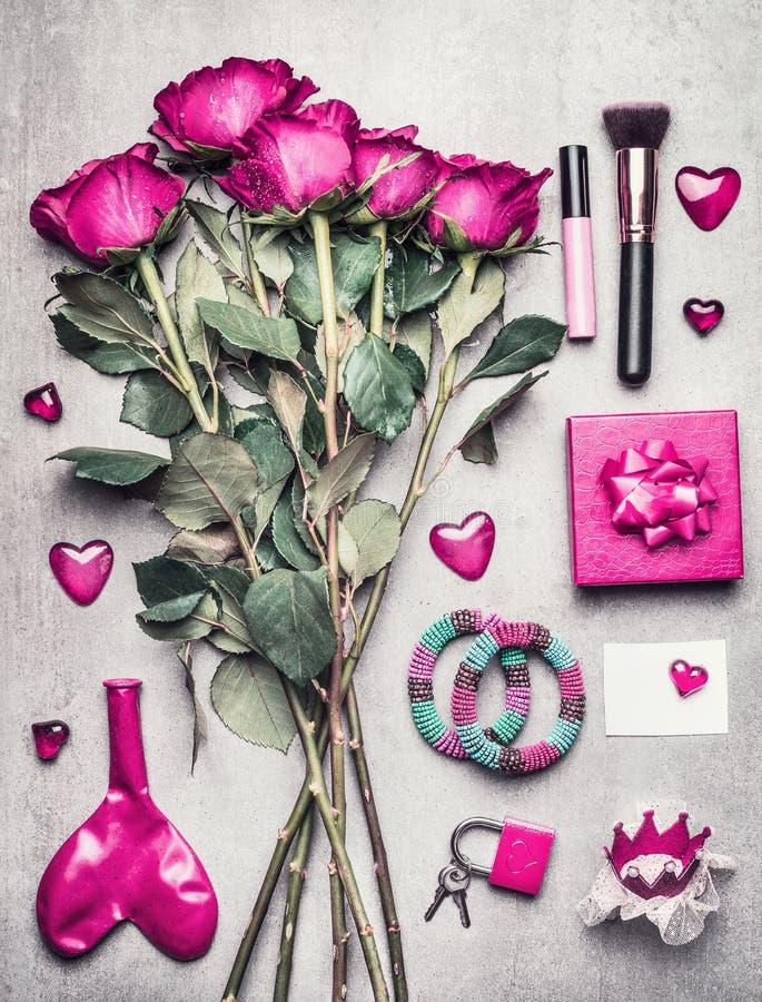 Os acessórios fêmeas cor-de-rosa com rosas florescem, composição, corações Vista superior no boudoir desarrumado da mulher, no bl imagem de stock royalty free
