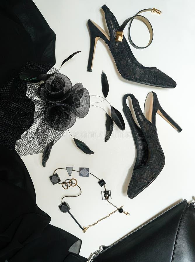 Os acessórios fêmeas da coleção do equipamento do partido de Dia das Bruxas enegrecem no fundo branco, sapatas, pano, joia, saco, imagem de stock