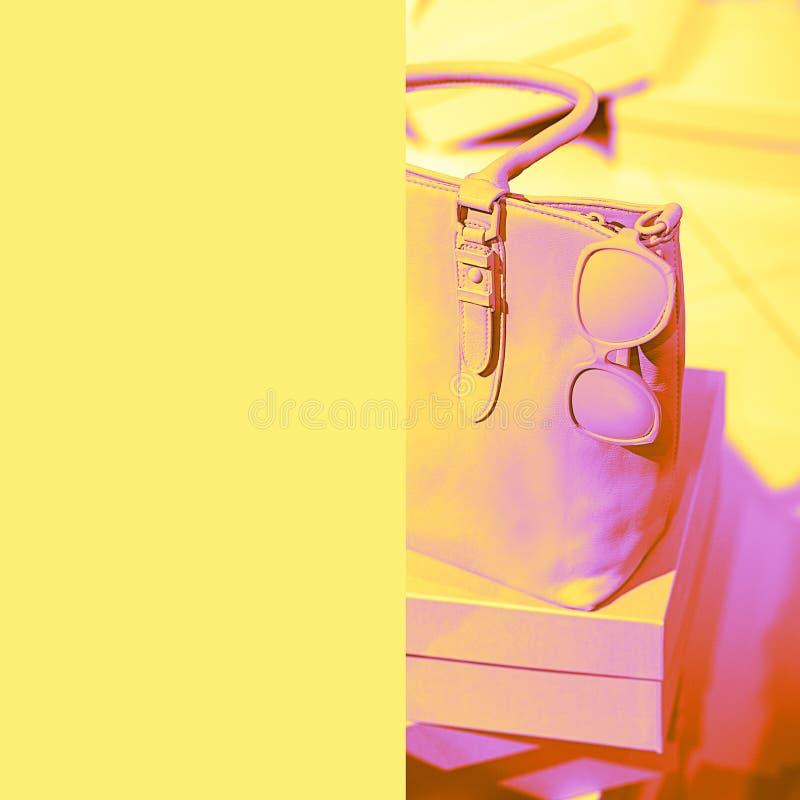 Os acessórios fêmeas na moda do conceito ensacam vidros em caixas e no fundo amarelo de néon vívido da cor Equipamento da forma d imagem de stock royalty free