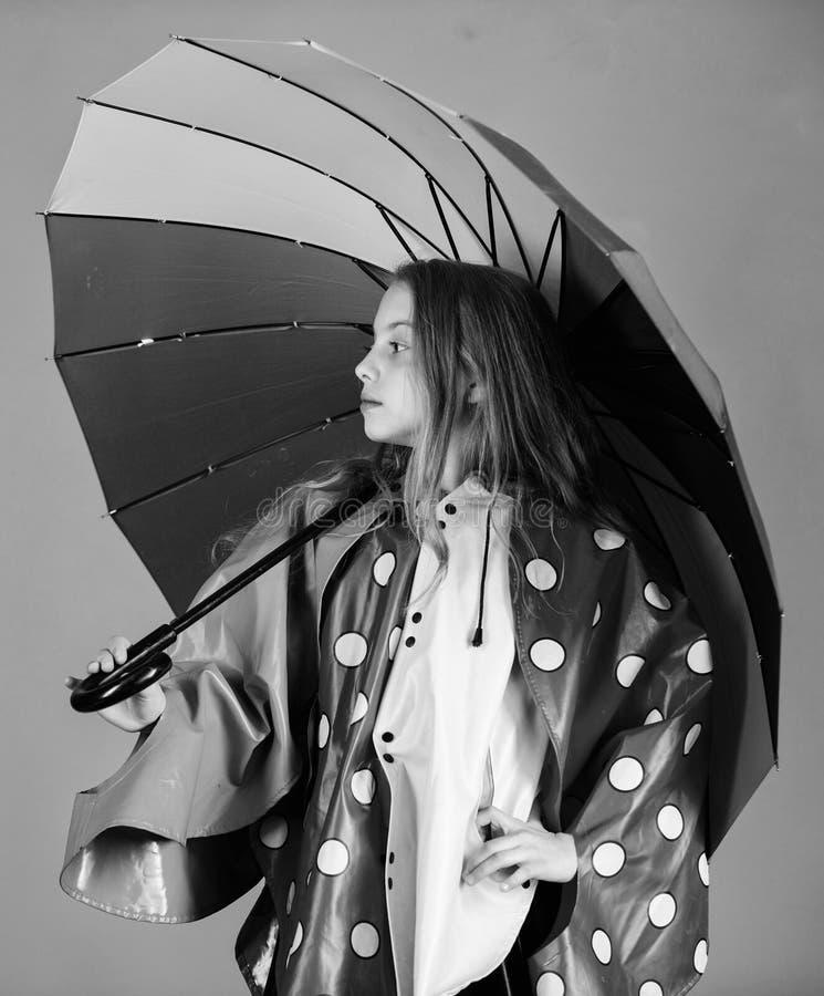 Os acessórios impermeáveis fazem o dia chuvoso alegre e agradável Guarda-chuva colorido da posse feliz da menina da criança para  imagem de stock
