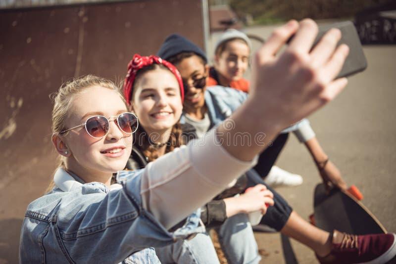 Os adolescentes agrupam a tomada do selfie do moderno ao sentar-se junto no parque do skate fotografia de stock royalty free
