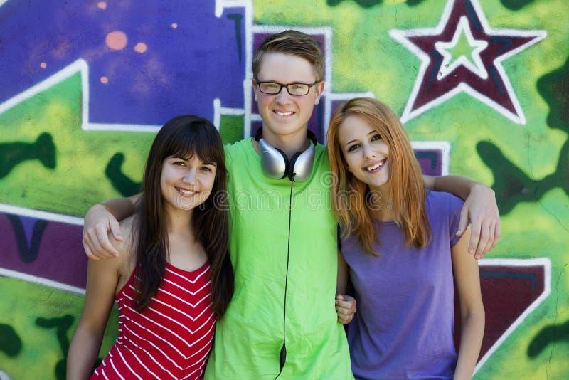 Os adolescentes com auscultadores aproximam a parede dos grafittis. imagens de stock