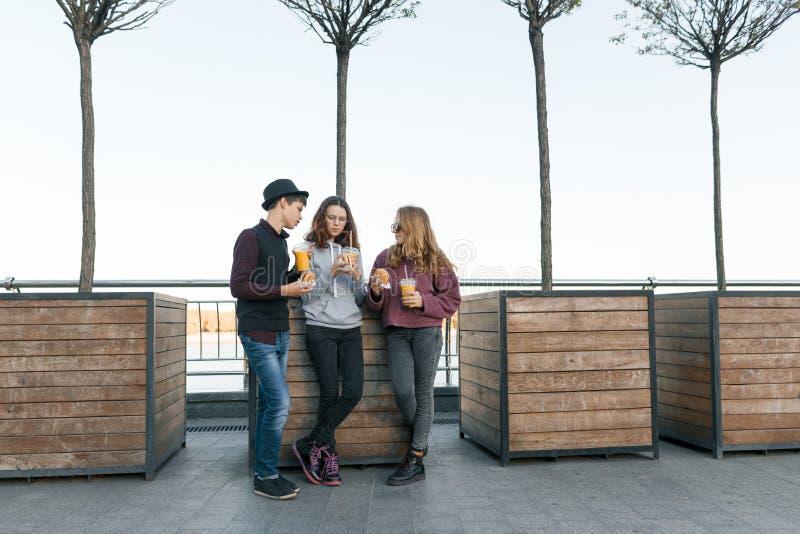 Os adolescentes comem o alimento da rua, o menino dos amigos e as duas meninas na rua da cidade com hamburgueres e suco de laranj imagem de stock