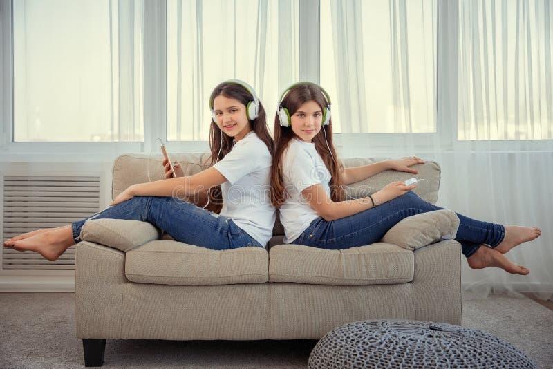 Os adolescentes das irmãs com telefone esperto e música de escuta dos fones de ouvido e comunicam-se em redes sociais imagem de stock royalty free