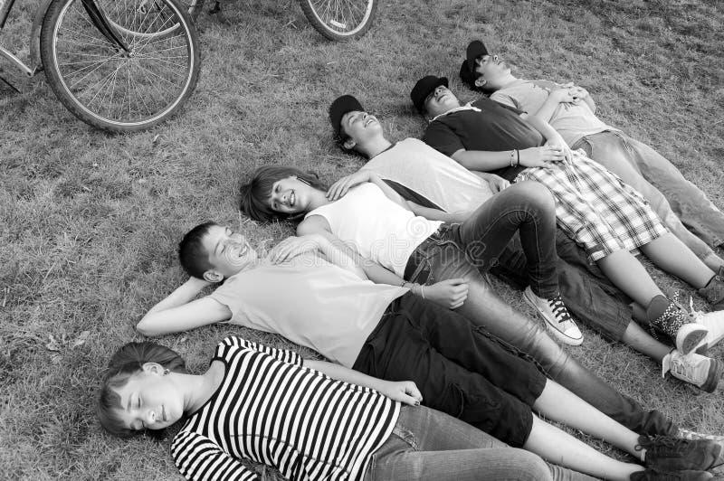 Os adolescentes e as meninas que encontram-se no prado da mola após a bicicleta montam foto de stock royalty free