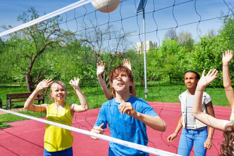 Os adolescentes estão jogando o voleibol perto da rede fotografia de stock