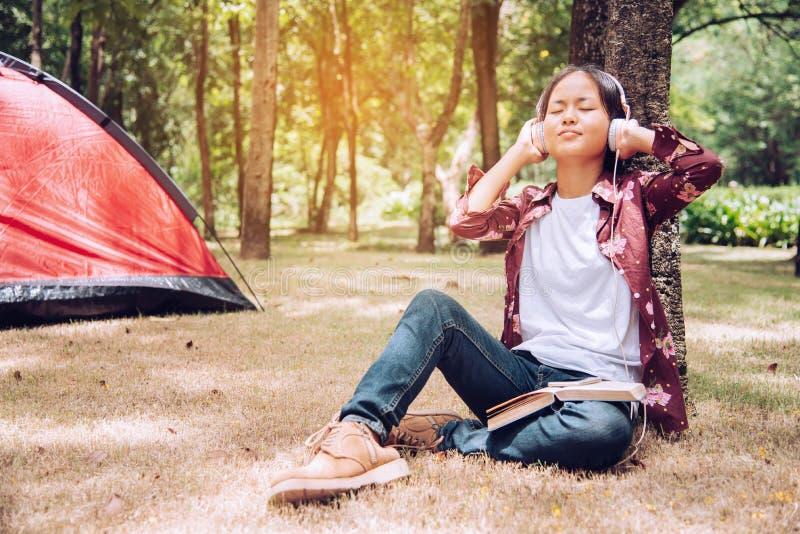 Os adolescentes estão relaxando e felizes escutando a música no piquenique imagem de stock