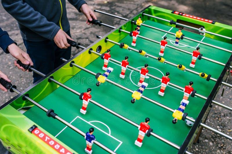 Os adolescentes jogam o futebol da tabela na rua Um jogo do futebol da tabela Jovens que jogam o ar livre do jogo de mesa no ver? foto de stock
