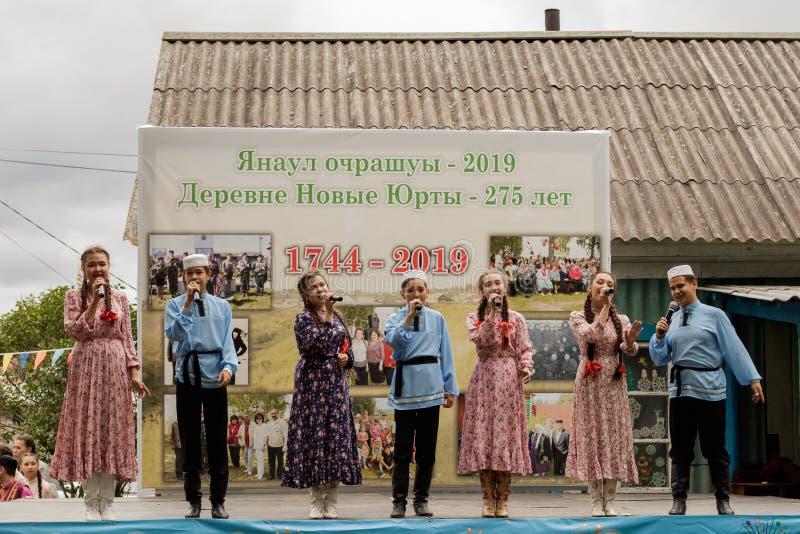 Os adolescentes na roupa Tatar tradicional cantam na fase contra o contexto de um suporte com fotografias históricas Vila do feri imagens de stock