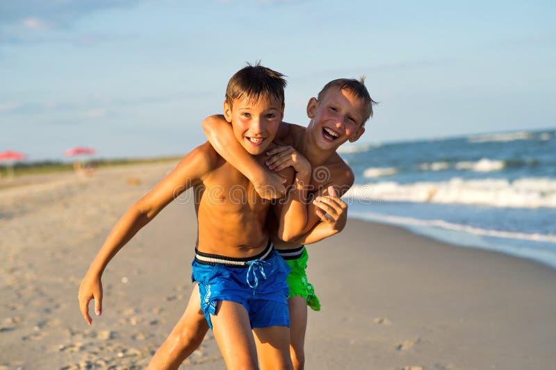 Os adolescentes que jogam no mar encalham no verão foto de stock