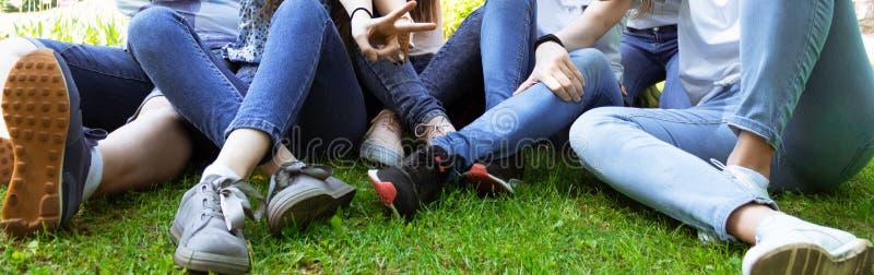 Os adolescentes sentam-se nas calças de brim e nas sapatilhas na grama Conceito do verão fotos de stock