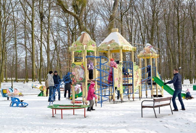 Os adultos jogam com as crianças no campo de jogos no parque do inverno Kaliningrad imagens de stock