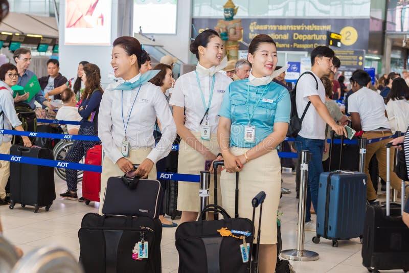Os aeromoços do ` s de Korean Air esperam felizmente para verificar seu lugg imagens de stock
