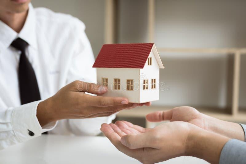 Os agentes da casa estão dando presentes da casa aos compradores de casa novos na sala do escritório fotografia de stock
