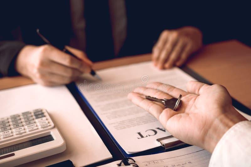 Os agentes da casa estão distribuindo chaves aos compradores de casa que estão assinando contratos no escritório imagem de stock