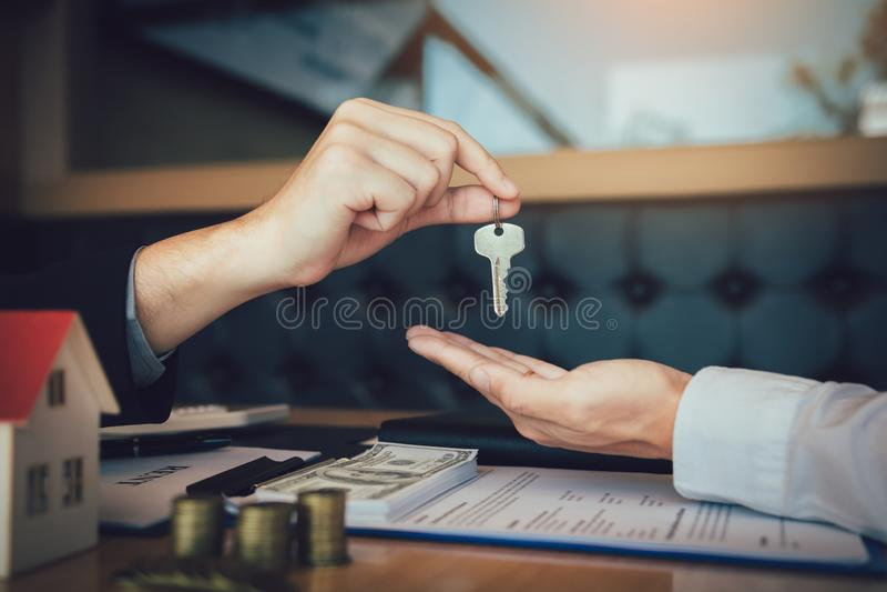 Os agentes da casa estão distribuindo chaves aos compradores de casa que estão assinando contratos no escritório fotos de stock