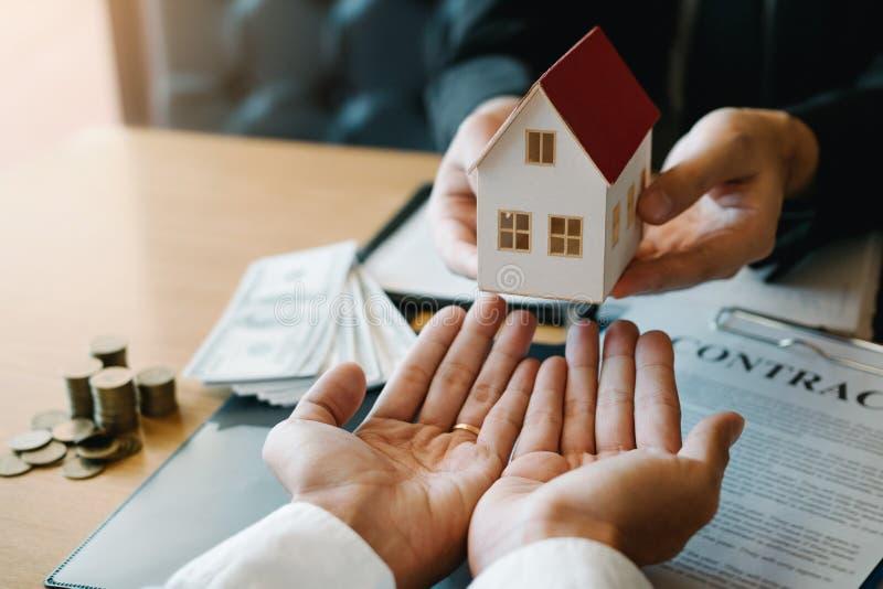 Os agentes da casa est?o dando presentes da casa aos compradores de casa novos na sala do escrit?rio imagem de stock royalty free
