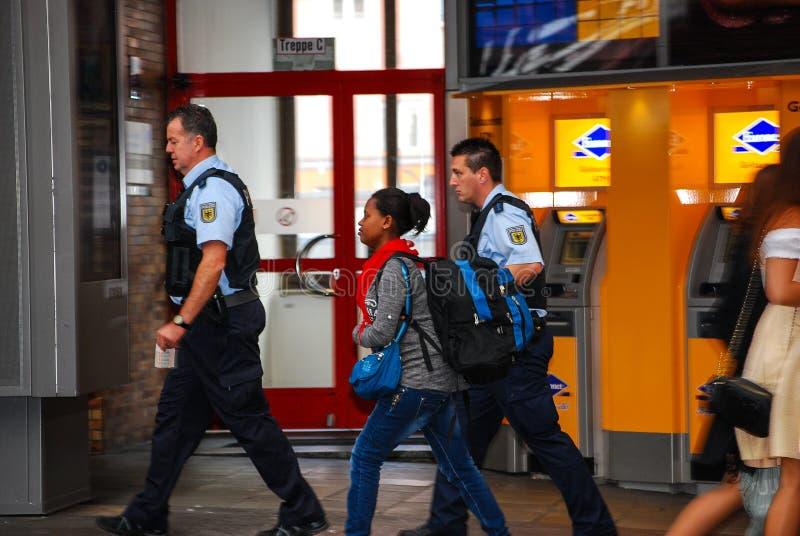 Os agentes da polícia acompanham uma mulher emigrante de chegada foto de stock royalty free