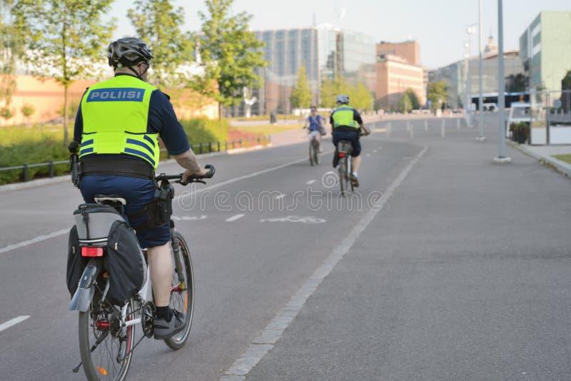 Os agentes da polícia em bicicletas patrulham as ruas em Helsínquia, Finlandia foto de stock