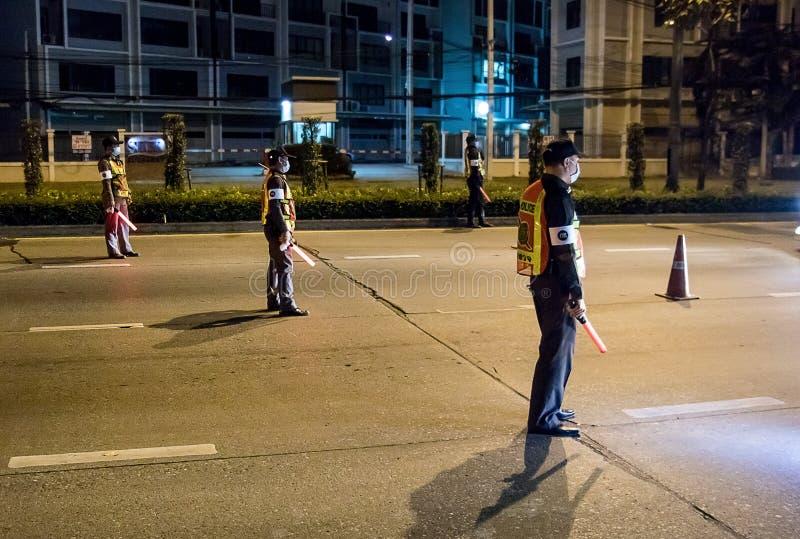 Os agentes da polícia inspecionam carros na estrada da noite de Banguecoque imagens de stock