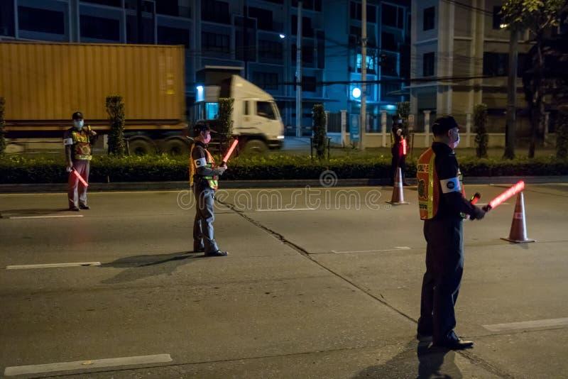 Os agentes da polícia inspecionam carros na estrada da noite de Banguecoque fotos de stock